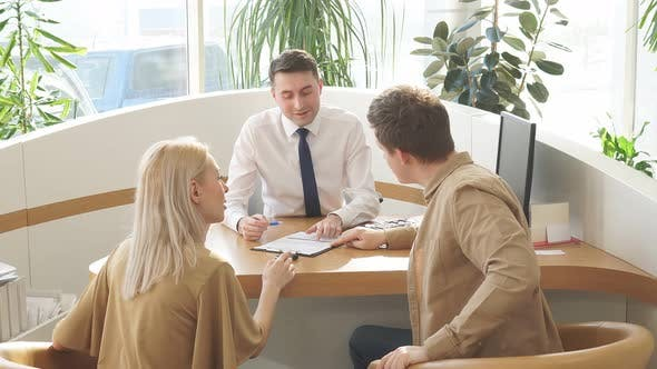 Helpful Consultant Have Conversation with Customers at Table.
