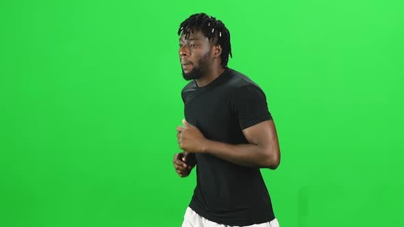 Thumbnail for Portrait of African American Man with Dreadlocks Is Running at Green Screen, Chroma Key