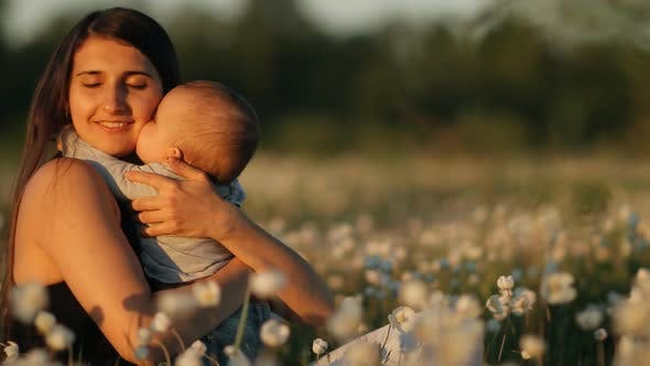 Thumbnail for Slow Motion of a Young Happy Mother and Child in a Flower Field at Sunset.