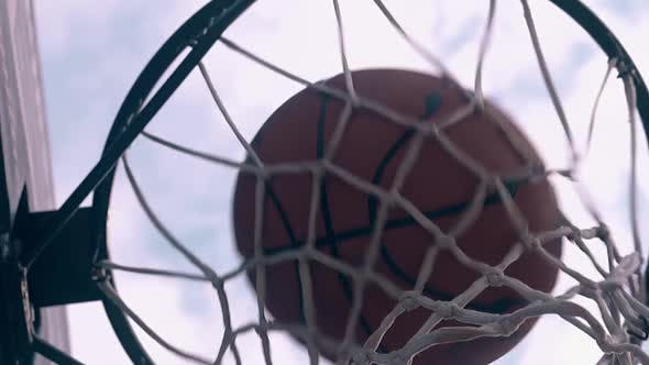 Throwing Ball Into Basket Against Sky with Clouds Closeup