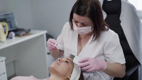 Kosmetikerin macht kosmetologische Ultraschall-Gesichtsreinigung für eine junge Frau