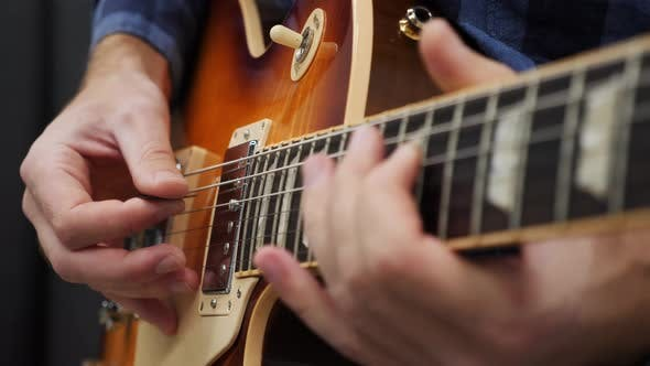Hands playing on guitar