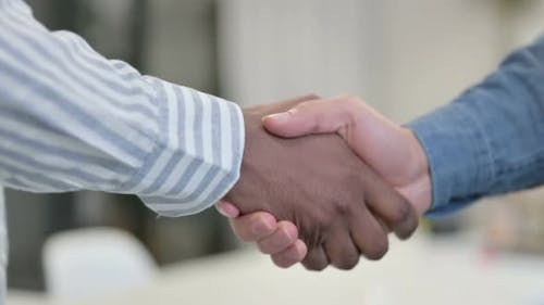 Close Up of African Man Shaking Hands with White Man