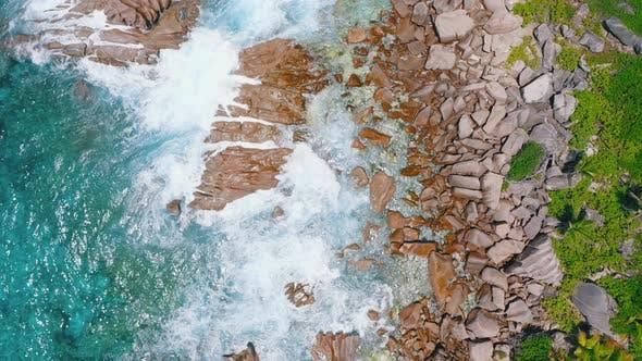 Thumbnail for Aerial Bird Eye View Footage of Waves Hitting Splashed the Coastline Granite Rocks