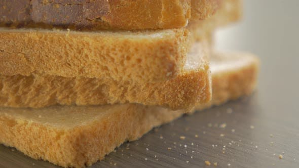 Bread pieces arranged on table top close-up tilting 4K 2160p UltraHD footage - Toast bread on table