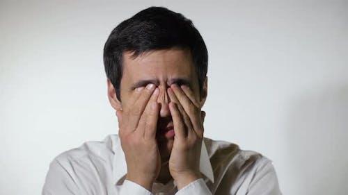 Tired Man Rubs His Eyes