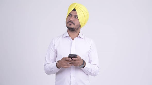 Thumbnail for Happy Bearded Indian Sikh Businessman Thinking While Using Phone