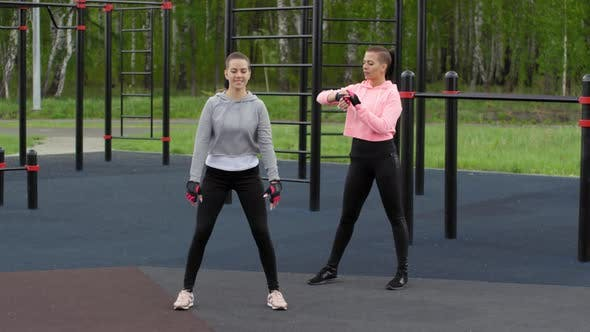 Thumbnail for Young Caucasian Woman Doing Squats in Park and Twin Sister Counting