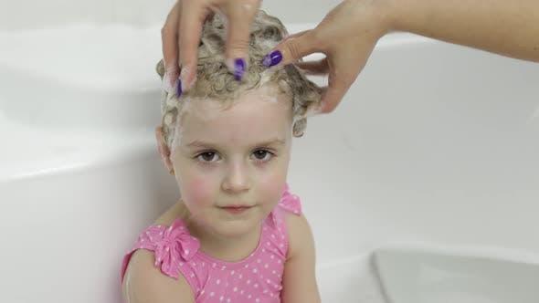 Thumbnail for Niedlich blonde Mädchen nimmt ein Bad in Bademode. kleine Kind wäscht Ihr Kopf
