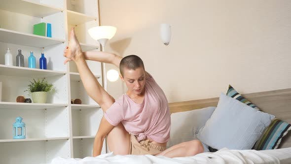 Confident Athletic Young Woman Sitting on Bed Doing Stretch After Workout at Home
