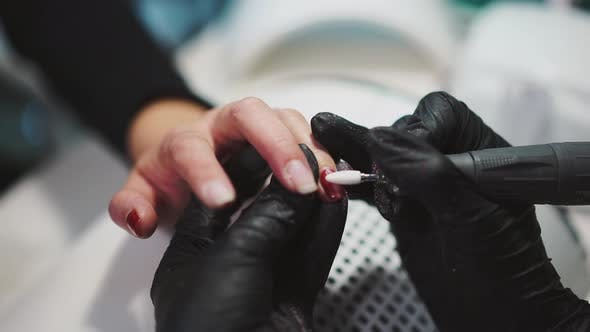 Thumbnail for Manicurist is Removing Red Gel Polish From the Client's Fingers