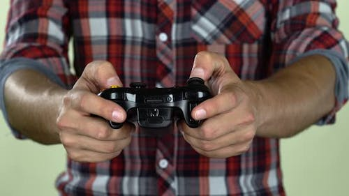 Hands of Dedicated Gamer Using a Game Controller