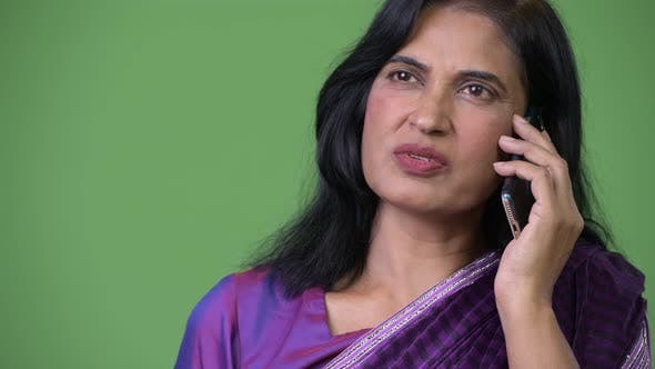 Thumbnail for Close Up Shot of Mature Beautiful Indian Woman Talking on the Phone While Thinking
