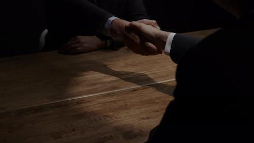 Business partners making handshake after secret meeting