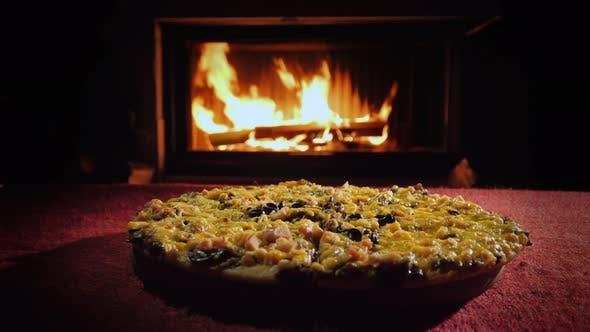 Appetitliche Pizza auf einer roten Tischdecke auf dem Hintergrund des Kamins, wo das Feuer brennt