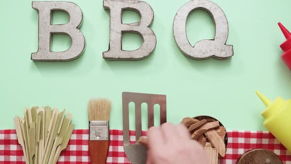 Metal BBQ sign with grilling tools on blue background.