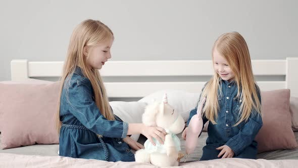 Two Cute Little Sisters Playing on Bed with Pillows