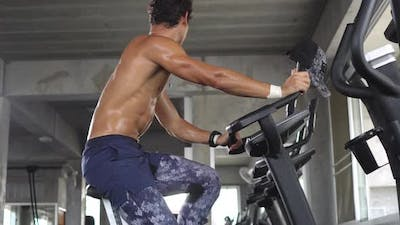 Athlete man cardio riding on bicycle at fitness