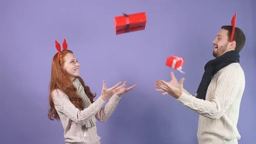 Young Beautiful Couple Throws Various Christmas Gifts in the Studio on a Black Background.