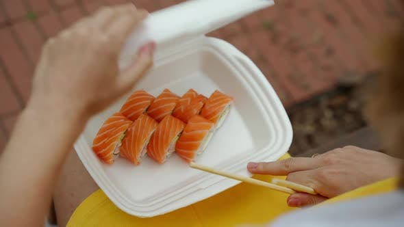 Thumbnail for Opens the Package with Rolls and Sushi and Hands Takes Them