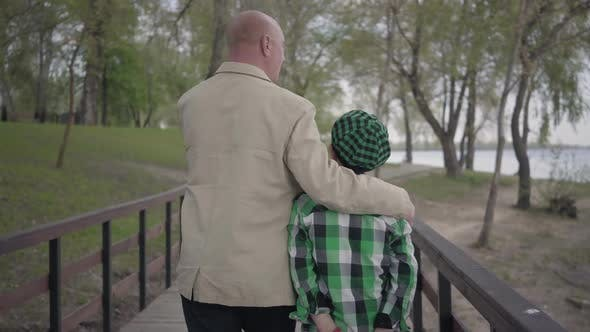 Thumbnail for Back View of Grandfather and Grandson Walking on the Bridge in the Park with Their Backs