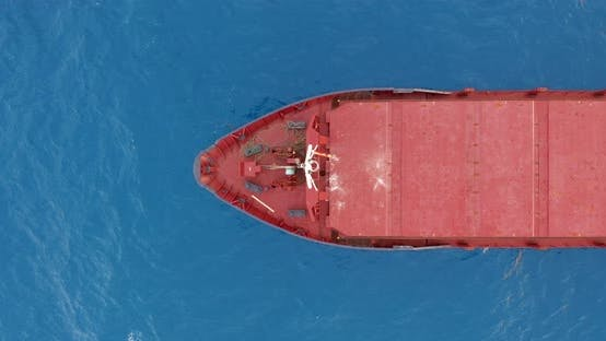 Aerial View. Red Deck Cargo Ship Sailing on Open Sea.
