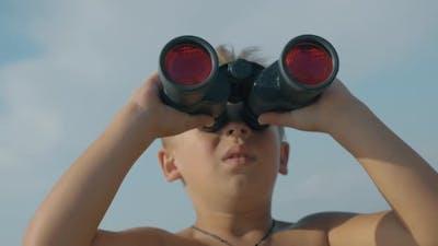 Child exploring the world with binoculars