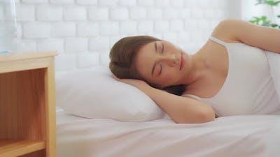 Asian woman wearing Pajamas sleep close her eyes smile sleep and sweet dream