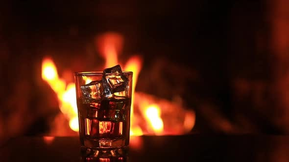 Thumbnail for Glass of Whiskey with Ice Near the Fireplace