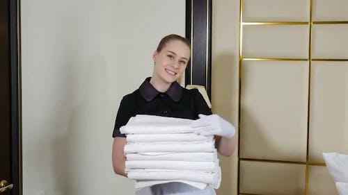 Vorbereitung des Hotelzimmers. Zimmermädchen Aufräumen in der Hotel-Suite und Bringen paar saubere frische Handtücher für