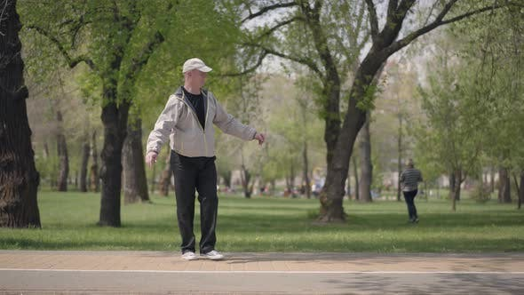 Thumbnail for Little Boy in Checkered Shirt Rollerblading in the Park, His Grandfather Catching Him and Hugging