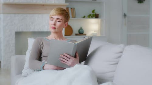 Calm Relaxed Woman Holding Reading Book Sitting on Sofa 35 s Millennial Female Reader Enjoying