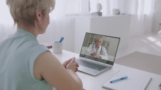 Thumbnail for Woman Is Calling Doctor By Video Conference From Home, Aged Experienced Professor of Medicine Is