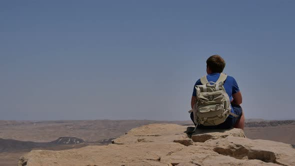 Thumbnail for Young Man with Backpack Sitting on Cliff's Edge and Enjoying the Desert View