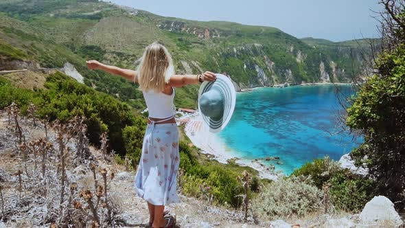 Thumbnail for Slow Mo of Beautiful Blond Women Holding Sun Hat and Raising Her Hands on Vacation at Kefalonia