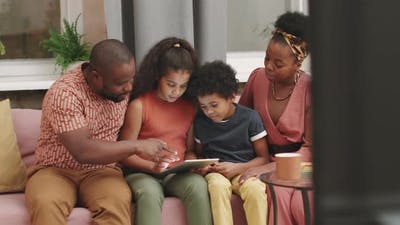 Afro Family Playing Games On Tablet Together