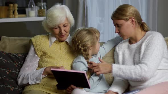 Thumbnail for Mother and Grandmother Looking at Family Picture with Little Girl