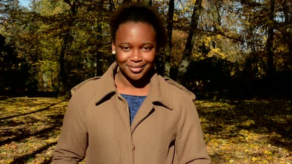 Thumbnail for Young Beautiful African Happy Girl Stand in Woods, Stare To Camera and Nods Head