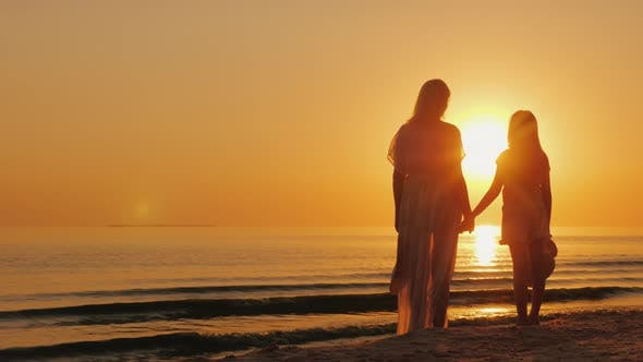 Thumbnail for Mom and Daughter of Seven Years Together Look at the Beautiful Sunset Over the Sea