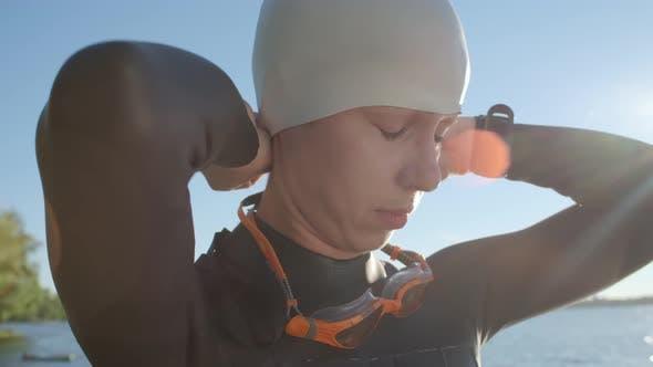 Thumbnail for Female Swimmer Putting on Swim Cap