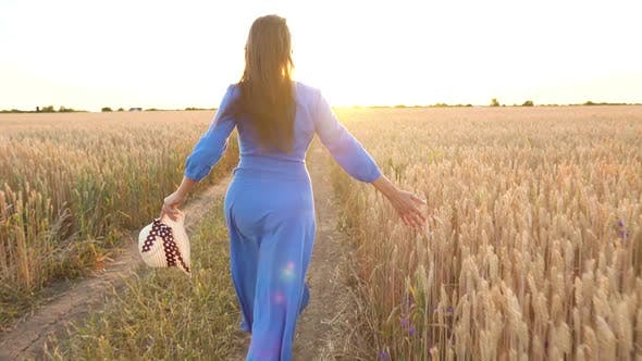 Beautiful Woman in a Blue Dress and Hat Runs Through a Wheat Field at Sunset