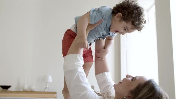 Smiling Single Mother Raising Little Son Up at Home