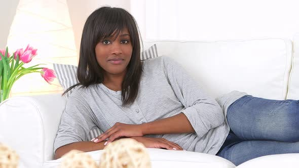 Thumbnail for Casual black woman lounging on couch
