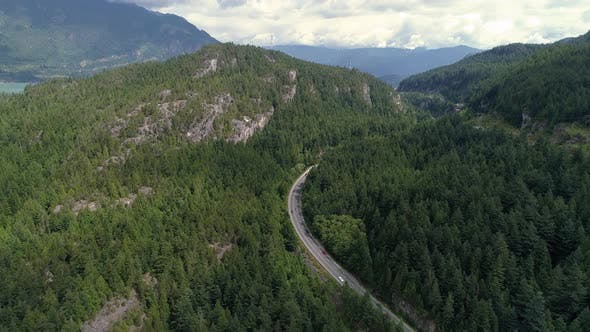 Thumbnail for Helicopter View Of Cars Traveling Scenic Highway Into Thick Green Forest Mountains