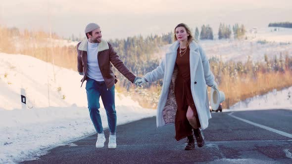 a Couple Walking on a Car Road