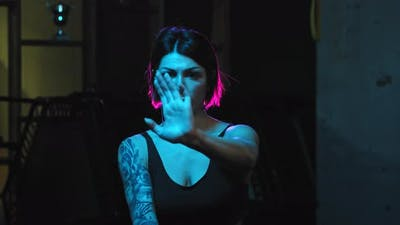 A Strong Tattooed Woman Showing Karate Moves in Neon Lighting