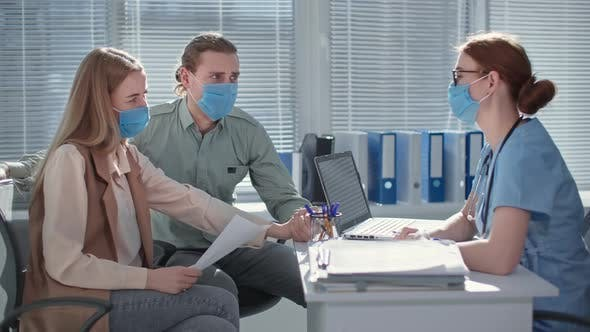 Professional Doctor in Medical Mask to Protect Against Virus and Infection Consults Married Couple