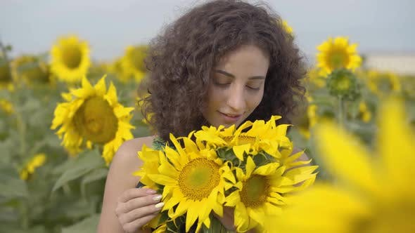 Thumbnail for Portrait of Adorable Curly Playful Girl Looking at the Camera Smiling Standing in the Sunflower