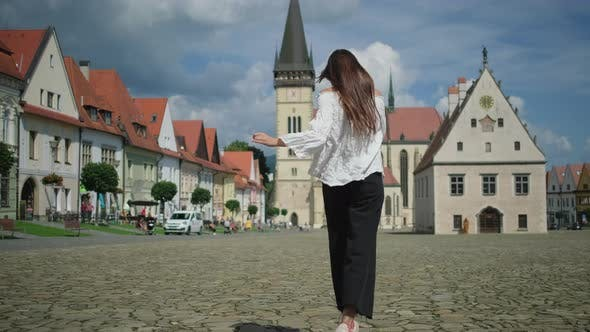Tourist Woman is Running Over Town Hall Square in Bardejov in Slovakia