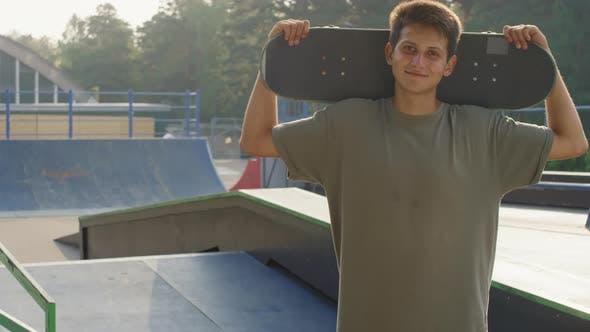 Portrait of Happy Guy with Skateboard